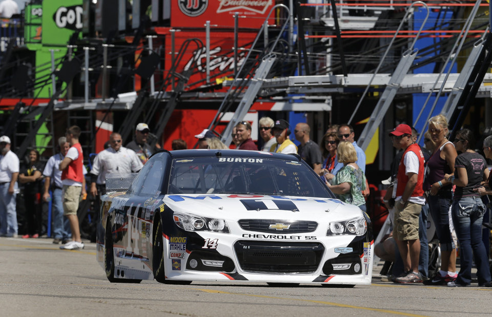 Photo - Jeff Burton drives Tony Stewart's No. 14 car through the garage to to practice for the NASCAR Sprint Cup Series auto race at Michigan International Speedway in Brooklyn, Mich., Friday, Aug. 15, 2014. A