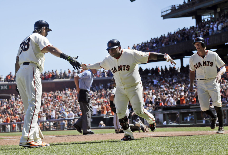 Photo - San Francisco Giants' Pablo Sandoval, center, celebrates his two-run home run with teammate Michael Morse, left, during the fifth inning of a baseball game against the Milwaukee Brewers, Sunday, Aug. 31, 2014, in San Francisco. (AP Photo/Marcio Jose Sanchez)