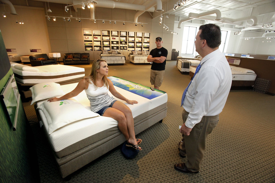 Salesman George Rea, right, talks with customers Sarah Foster and Rob Juby at Mathis Brothers� new Sleep Studio in Norman.Photo by STEVE SISNEY, THE OKLAHOMAN