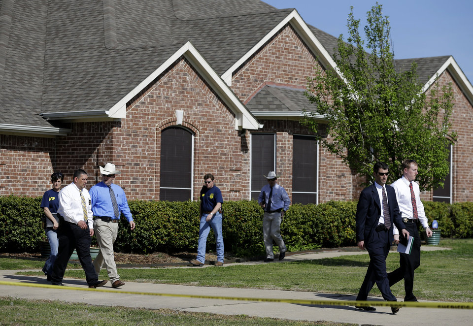Photo - Law enforcement officials walk out of the home of Kaufman District Attorney Mike McLelland Monday, April 1, 2013, near Forney, Texas. McLelland and his wife were both murdered at their home Saturday. (AP Photo/Tony Gutierrez)