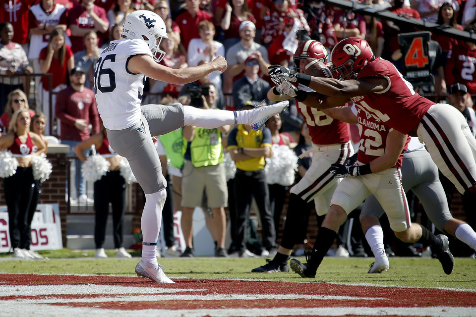 Photo - Oklahoma's Brayden Willis (81) blucks the punt of West Virginia's Josh Growden (96) during a college football game between the University of Oklahoma Sooners (OU) and the West Virginia Mountaineers at Gaylord Family-Oklahoma Memorial Stadium in Norman, Okla, Saturday, Oct. 19, 2019. Oklahoma won 52-14. [Bryan Terry/The Oklahoman]