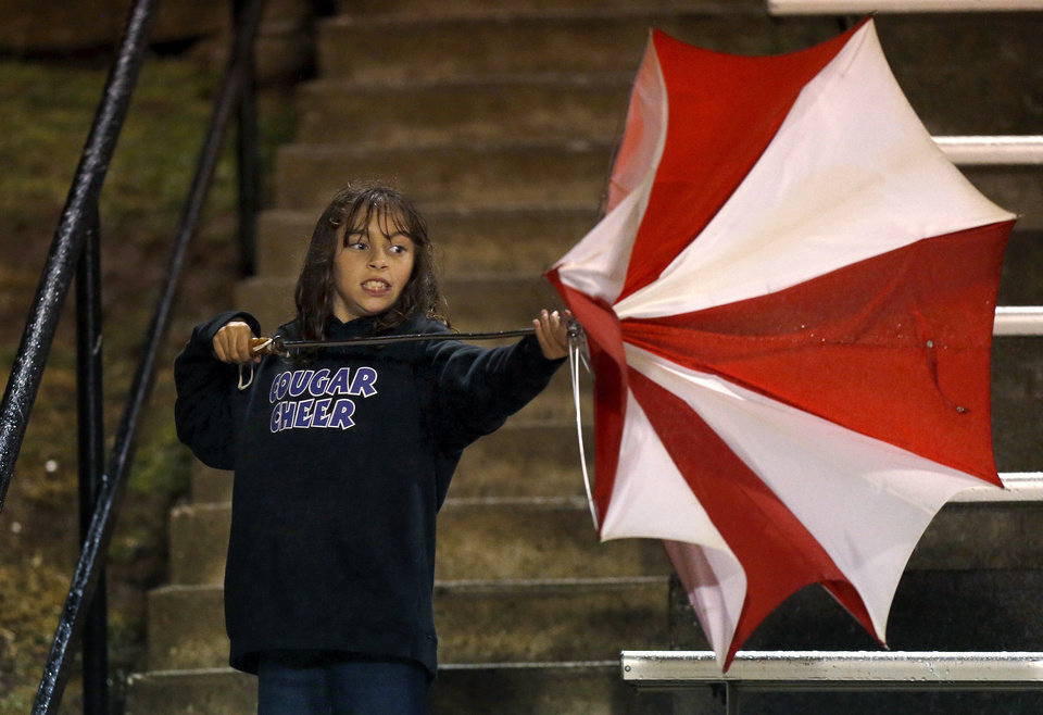 Alex Manning, 10, of Moore tries to adjust an umbrella during a high school football game between Westmoore and Norman North in Moore, Okla., Thursday, September 13, 2012. Photo by Bryan Terry, The Oklahoman