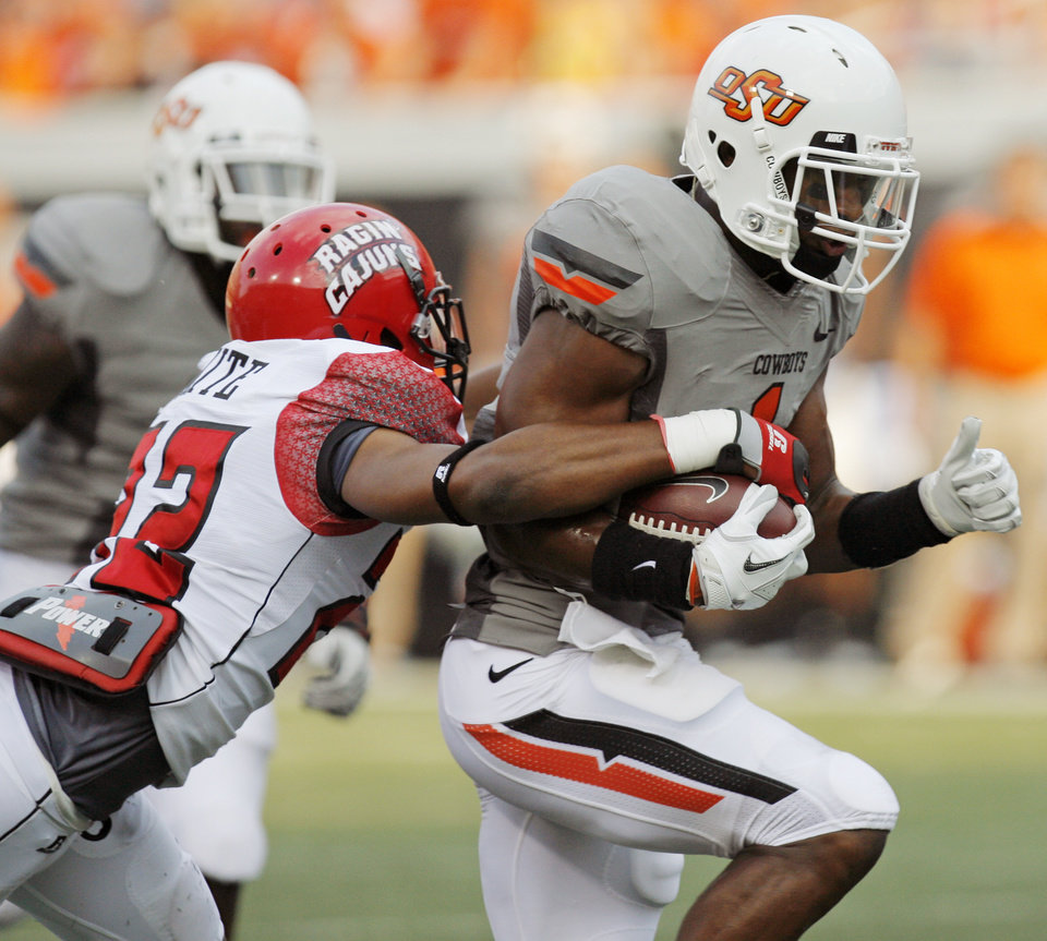 Photo - OSU's Joseph Randle tries to break away from ULL's Melvin White in the first quarter of their game Saturday in Stillwater. Photo by Nate Billings, The Oklahoman