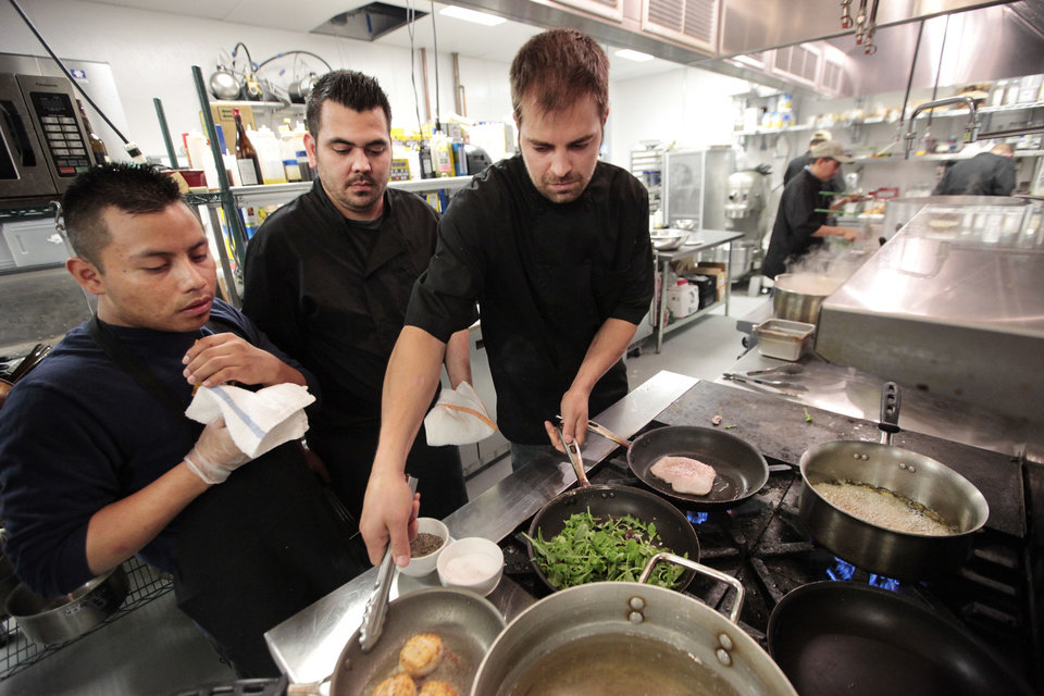 Photo -  Edwin Lopez, Executive Chef Mitchell Dunzy and Chris Horn prepare food in the kitchen at Packard's. Packard's is downtown's newest hot spot, a new concept for the classic space in Oklahoma City.  David McDaniel - The Oklahoman