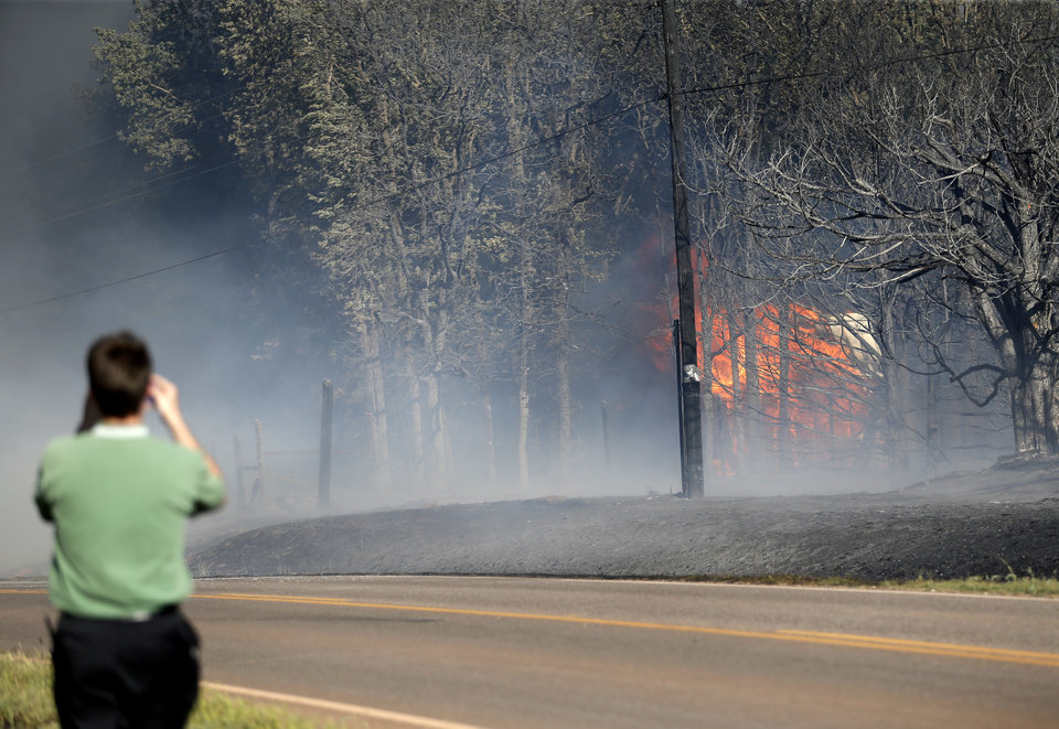 Photo - A man films a home burning as grassfire overtakes the area near East Seward Road and Oak Hill Road,  Sunday, May 4, 2014. Photo by Sarah Phipps, The Oklahoman