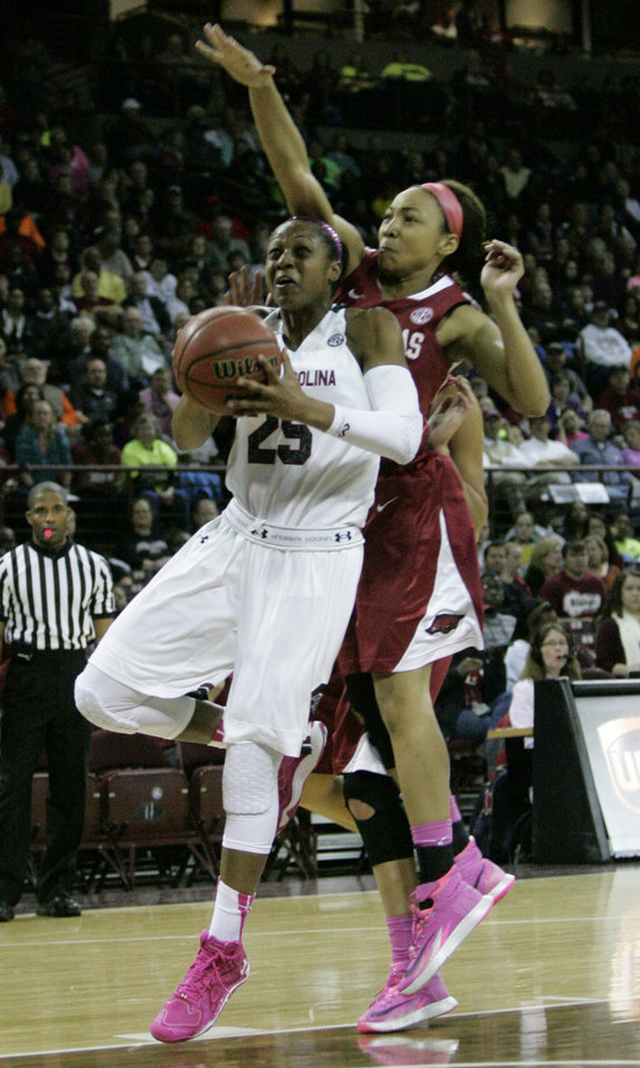 Photo - South Carolin's Tiffany Mitchell drives for the basket as Arkansas's Jessica Jackson is called for the foul as she tries to block the shot during an NCAA college basketball game on Sunday, Feb. 9, 2014, in Columbia, S.C. (AP Photo/Mary Ann Chastain)