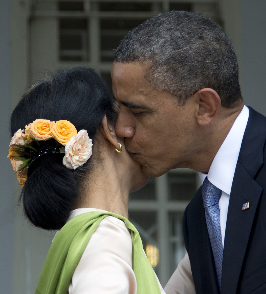 Photo -   U.S. President Barack Obama kisses Myanmar opposition leader Aung San Suu Kyi on the cheek after they spoke to press at her residence in Yangon, Myanmar, Monday, Nov. 19, 2012. Obama touched down Monday morning, becoming the first U.S. president to visit the Asian nation also known as Burma. (AP Photo/Carolyn Kaster)
