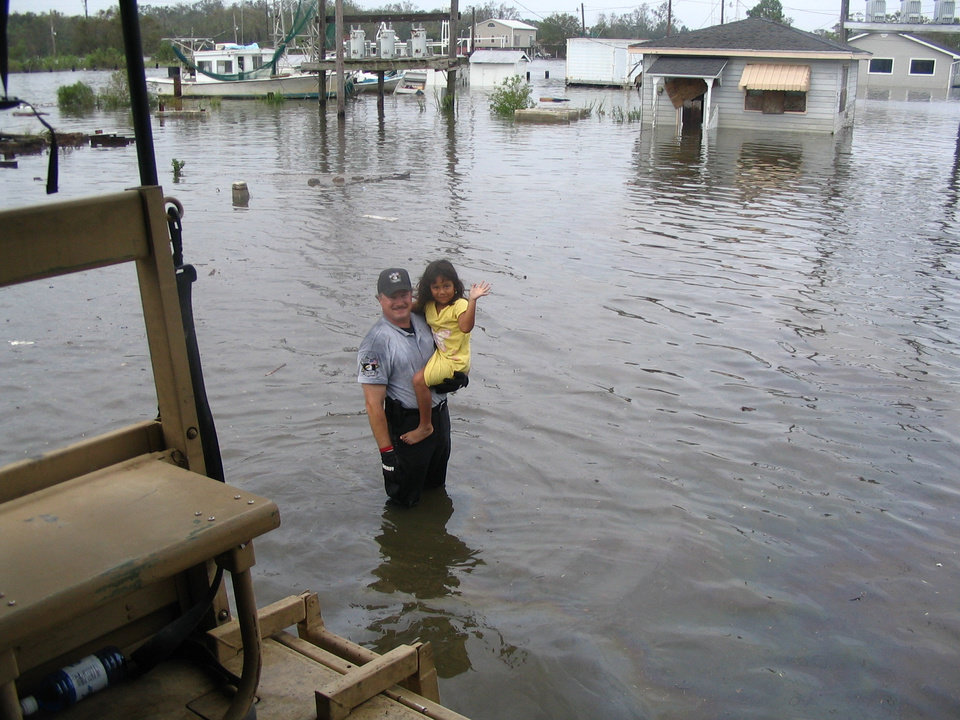 Photo -  Oklahoma County sheriff's reserve deputy Michael Davenport is shown with 5-year-old Hannah Verret after she was rescued from a boat with the rest of her family in the wake of Hurricane Rita. [Photo Provided]