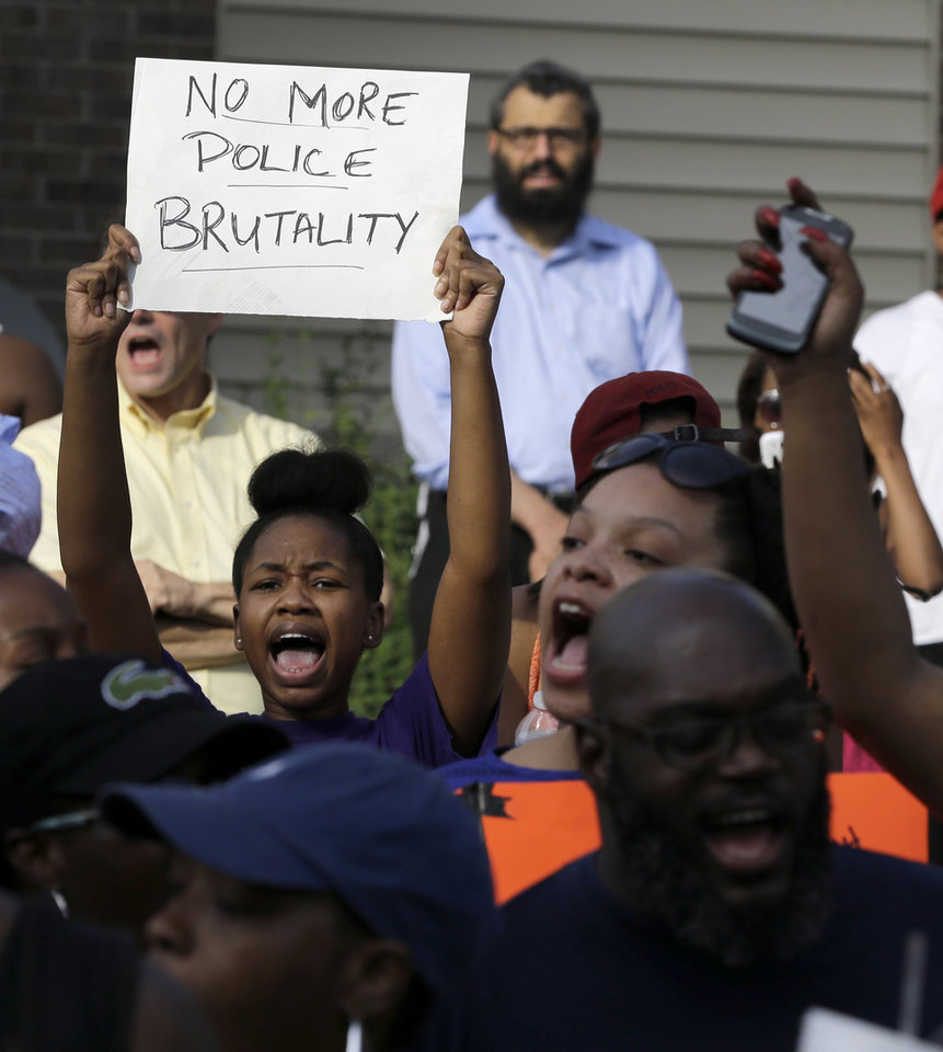 Photo - Demonstrators peacefully gather Thursday, Aug. 14, 2014, at the site where Michael Brown was shot and killed by police in Ferguson, Mo. The Missouri Highway Patrol seized control of a St. Louis suburb Thursday, stripping local police of their law-enforcement authority after four days of clashes between officers in riot gear and furious crowds protesting the death of an unarmed black teen shot by an officer. (AP Photo/Jeff Roberson)