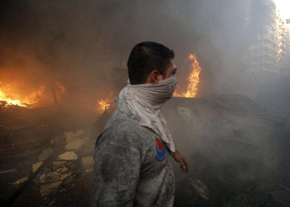 Photo - A Hezbollah civil defense worker walks past a burned car at a car bomb in the southern suburb of Beirut, Lebanon, Thursday, Aug. 15, 2013. The powerful car bomb ripped through a southern Beirut neighborhood that is a stronghold of the militant group Hezbollah on Thursday, killing at least three people and trapping others in burning buildings, the media said. (AP Photo/Hussein Malla)