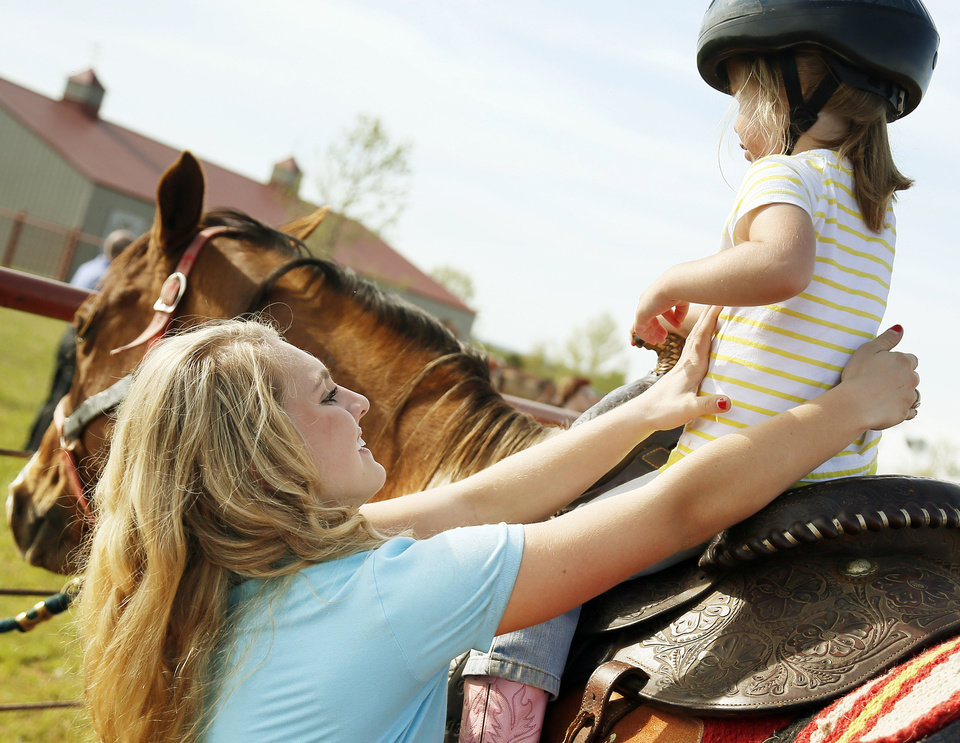 Photo - Molly Remondino, 17, helps Adyson Gray, 3, off a horse at the Peppers Ranch foster care community near Guthrie. Molly Remondino has started a teen board to help with the equine therapy program and other activities at the ranch. Photo by Nate Billings, The Oklahoman   NATE BILLINGS