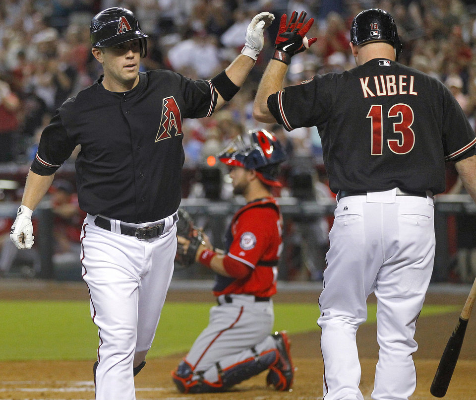 Photo -   Arizona Diamondbacks' Aaron Hill, left, celebrates with Jason Kubel (13) after hitting a solo home run during the first inning of a baseball game against the Washington Nationals, Saturday, Aug. 11, 2012, in Phoenix. Catching for Nationals is Jesus Flores. (AP Photo/Matt York)