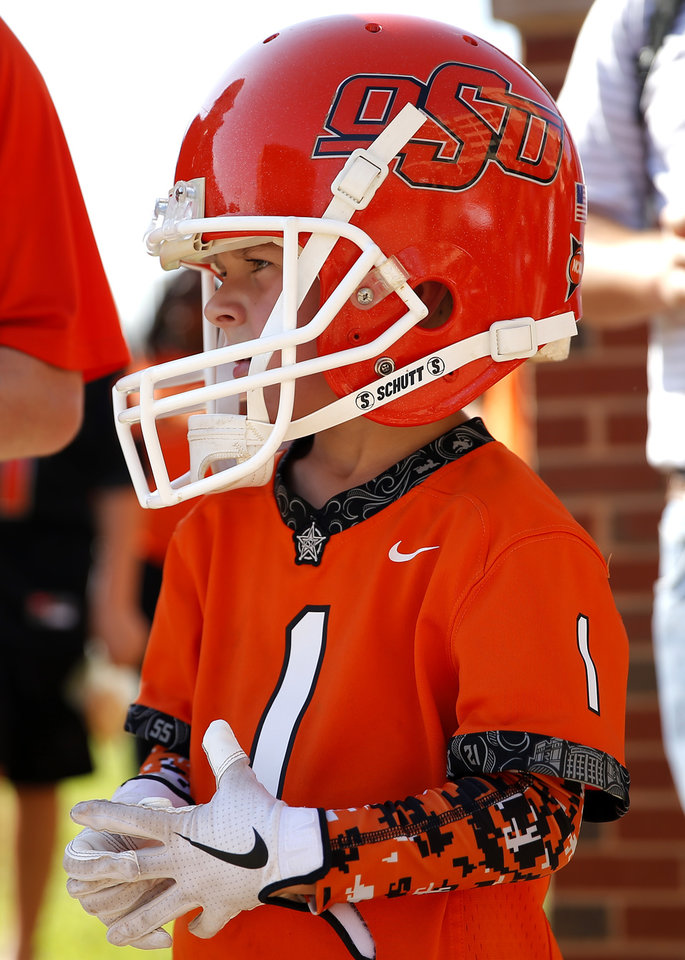 Photo - Bragen Smith, 6, of Tuttle, Okla., waits for players to walk during the walk before the college football game between the Oklahoma State Cowboys and the Kansas State Wildcats at Boone Pickens Stadium in Stillwater, Okla., Saturday, Sept. 28, 2019. [Sarah Phipps/The Oklahoman]