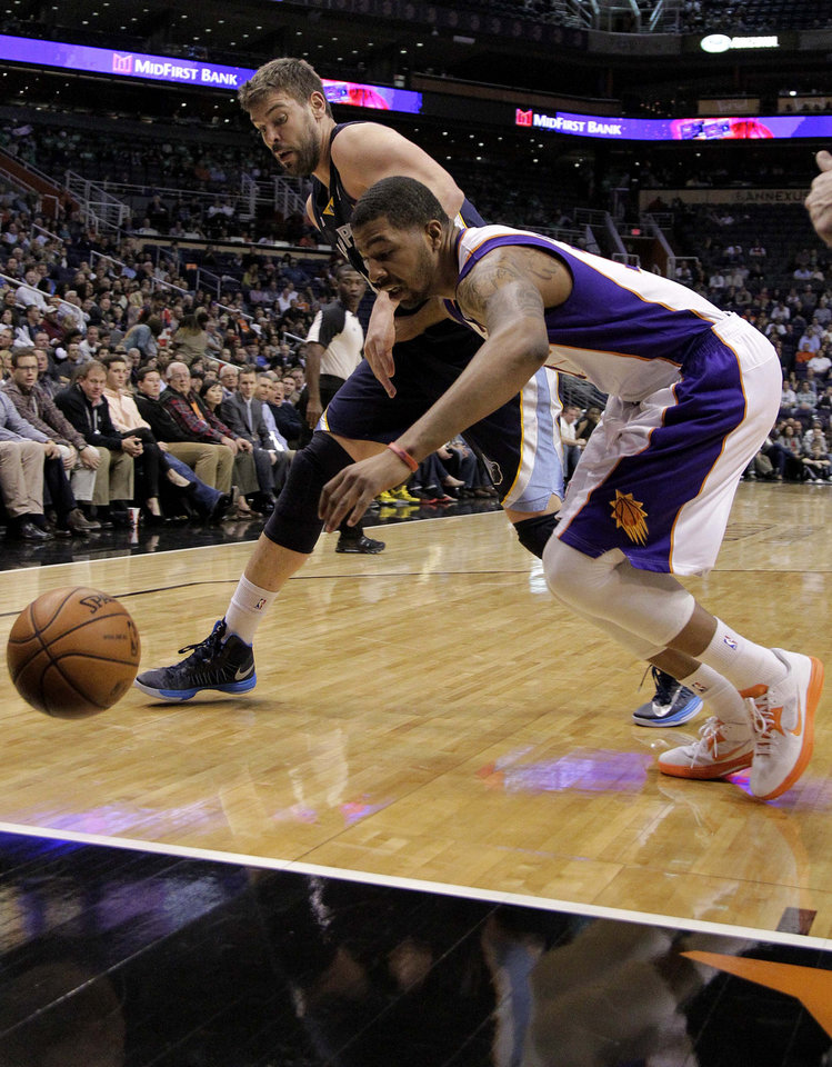 Memphis Grizzlies' Marc Gasol, left, of Spain, and  Phoenix Suns' Markieff Morris battle for a loose ball during the first half of an NBA basketball game on Wednesday, Dec. 12, 2012, in Phoenix. (AP Photo/Matt York)