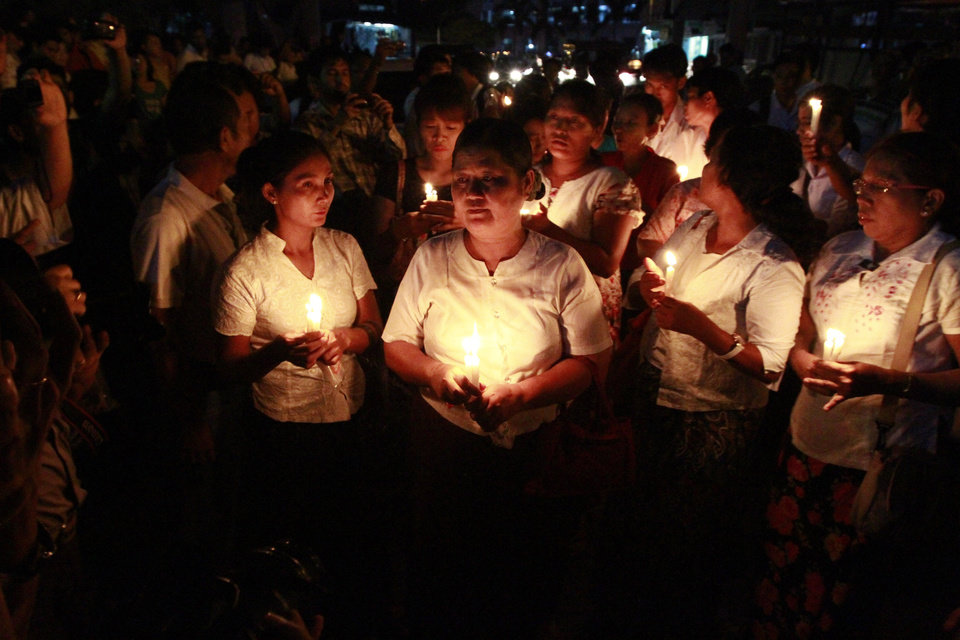 Photo -   Protesters hold candles during a candlelight vigil in downtown Yangon, Myanmar, Tuesday, May. 22, 2012. Myanmar's government made an uncharacteristic plea for understanding Tuesday after chronic power cuts set off rare protests in the Southeast Asian country that is easing toward democracy after decades of military rule. (AP Photo/Khin Maung Win)