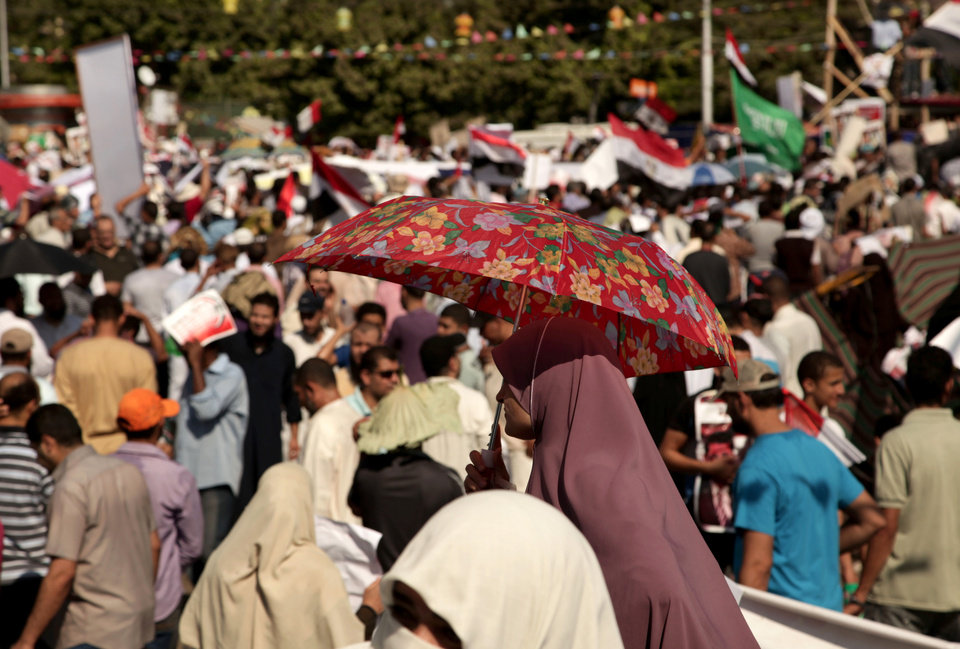 Photo - A supporter of Egypt's ousted President Mohammed Morsi holds an umbrella to protect her from the sun during a protest near Cairo University in Giza, Egypt, Friday, July 26, 2013. Egyptian prosecutors accused Morsi on Friday of conspiring with the Palestinian militant group Hamas and murder in his 2011 escape from prison that left 14 guards dead. The development fueled the likelihood of clashes as tens of thousands of supporters and opponents of the Islamist leader massed for rival rallies. (AP Photo/Nariman El-Mofty)