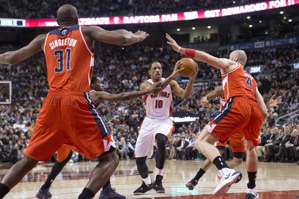 Photo - Toronto Raptors' DeMar DeRozan, center, drives at the Washington Wizards defense during first half NBA basketball action in Toronto, Thursday, Feb. 27, 2014. (AP Photo/The Canadian Press, Chris Young)
