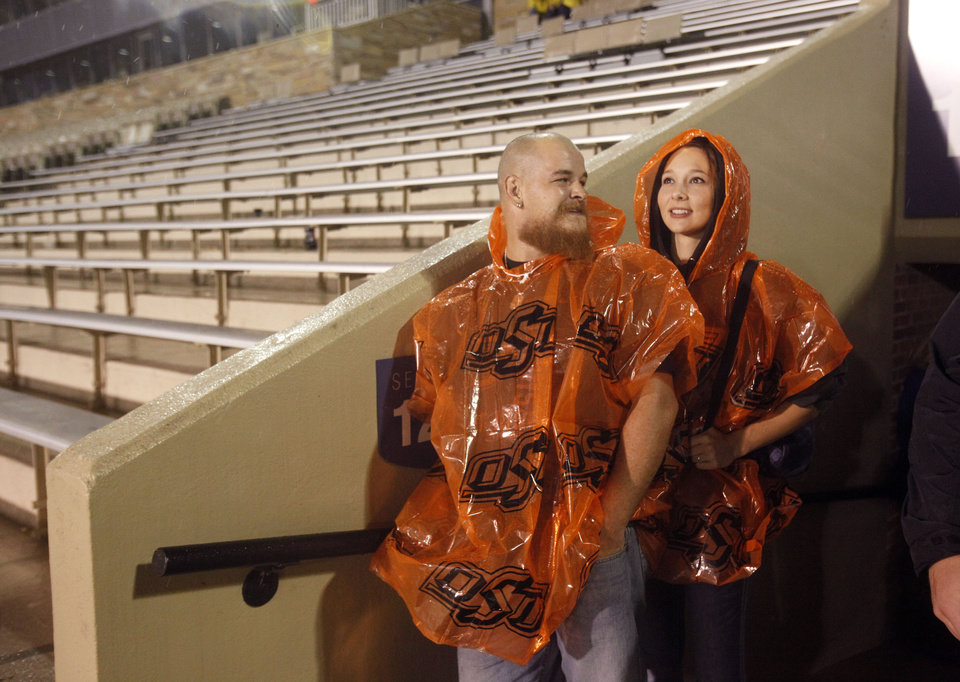 Tim Tandy and Brooke Umholt watch the rain before the OSU-Tulsa game on Saturday. Photo by Sarah Phipps, The Oklahoman