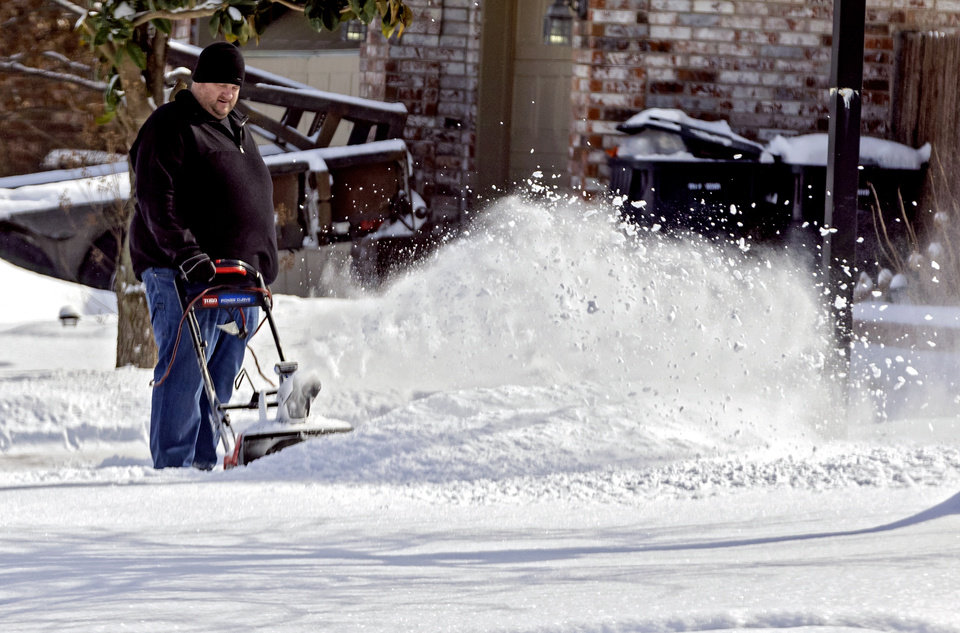 Photo - A person uses a snowblower to clear their driveway in Yukon, Okla. on Wednesday, Feb. 17, 2021.  [Chris Landsberger/The Oklahoman]