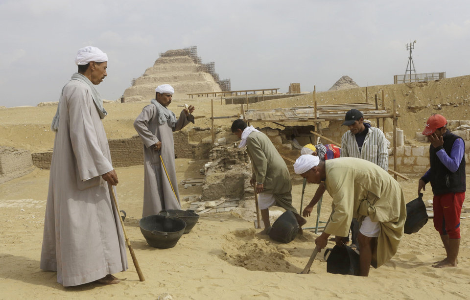 """Photo - Archaeology workers dig at the site of a newly-discovered tomb dating back to around 1100 B.C. at the Saqqara archaeological site, 30 kilometers (19 miles) south of Cairo, Egypt, Thursday, May 8, 2014. Antiquities Minister Mohamed Ibrahim said Thursday that the tomb belongs to a guard of the army archives and royal messenger to foreign countries. Ibrahim says the Cairo University Faculty of Archaeology's discovery at Saqqara adds """"a chapter to our knowledge about the history of Saqqara."""" Saqqara was the necropolis for the ancient Egyptian city of Memphis and site of the oldest known pyramid in Egypt.(AP Photo/Amr Nabil)"""