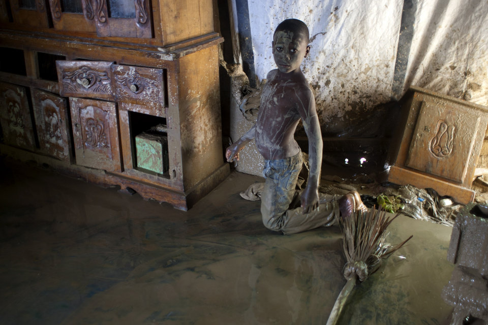 A boy looks at the camera as he cleans his flooded house after the passing of Tropical Storm Isaac in Port-au-Prince, Haiti, Sunday Aug. 26, 2012. The death toll in Haiti from Tropical Storm Isaac has climbed to seven after an initial report of four deaths, the Haitian government said Sunday. (AP Photo/Dieu Nalio Chery) ORG XMIT: PAP109