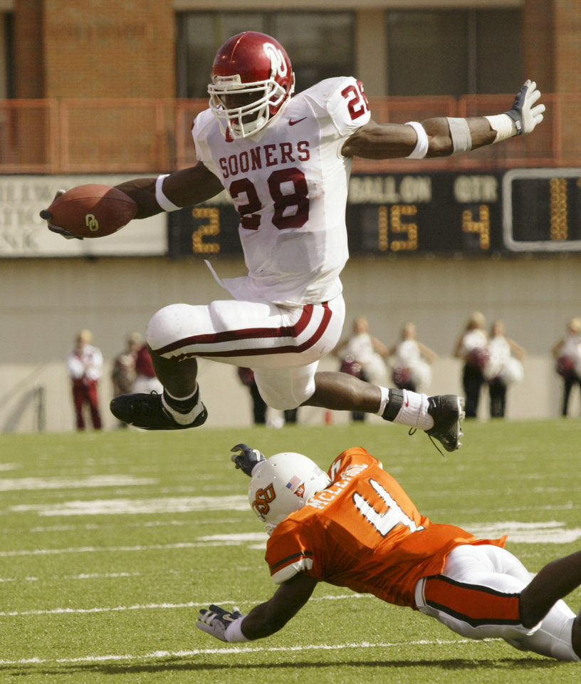 Photo -  OU's Adrian Peterson leaps over OSU's Daniel McLemore during the University of Oklahoma at Oklahoma State University Bedlam college football at Boone Pickens Stadium in Stillwater, Okla., October 30, 2004.  By Doug Hoke/The Oklahoman