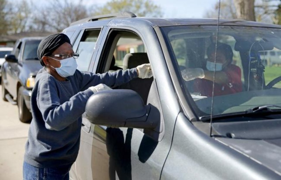 Photo - Pamela Walters hands out a form at a drive-thru food distribution for Oklahoma City school students outside The Market at Restore OKC in Oklahoma City, Thursday, March 26, 2020. The drive-thru food distribution was set up on site by Skyline Urban Ministry. [Bryan Terry/The Oklahoman]