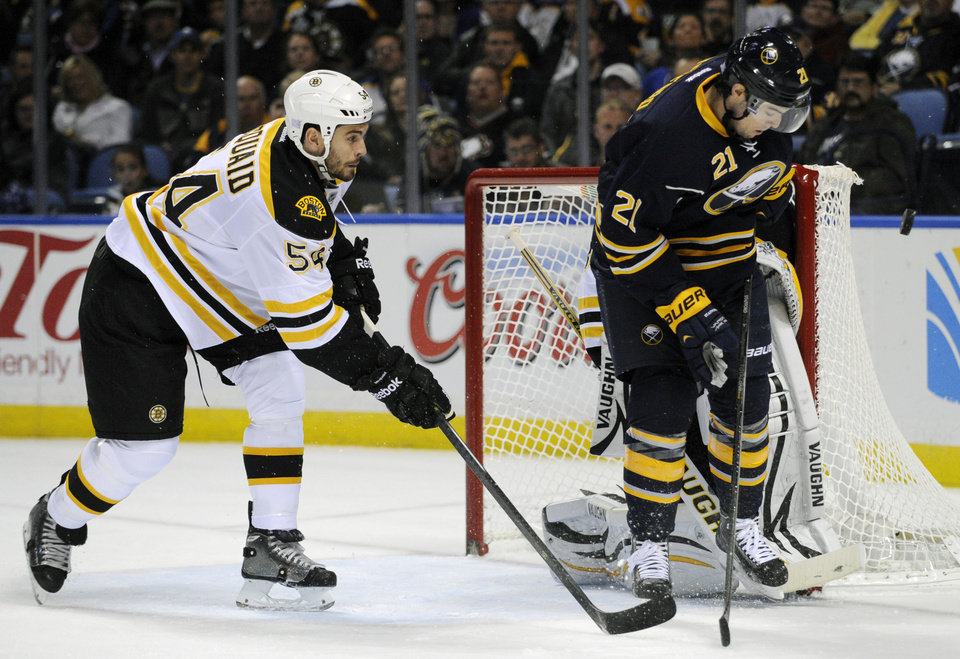 Photo - Boston Bruins defenseman Adam McQuaid (54) chases Buffalo Sabres right winger Drew Stafford (21) as he eyes an incoming shot during the first period of an NHL hockey game in Buffalo, N.Y., Wednesday, Oct. 23, 2013. (AP Photo/Gary Wiepert)