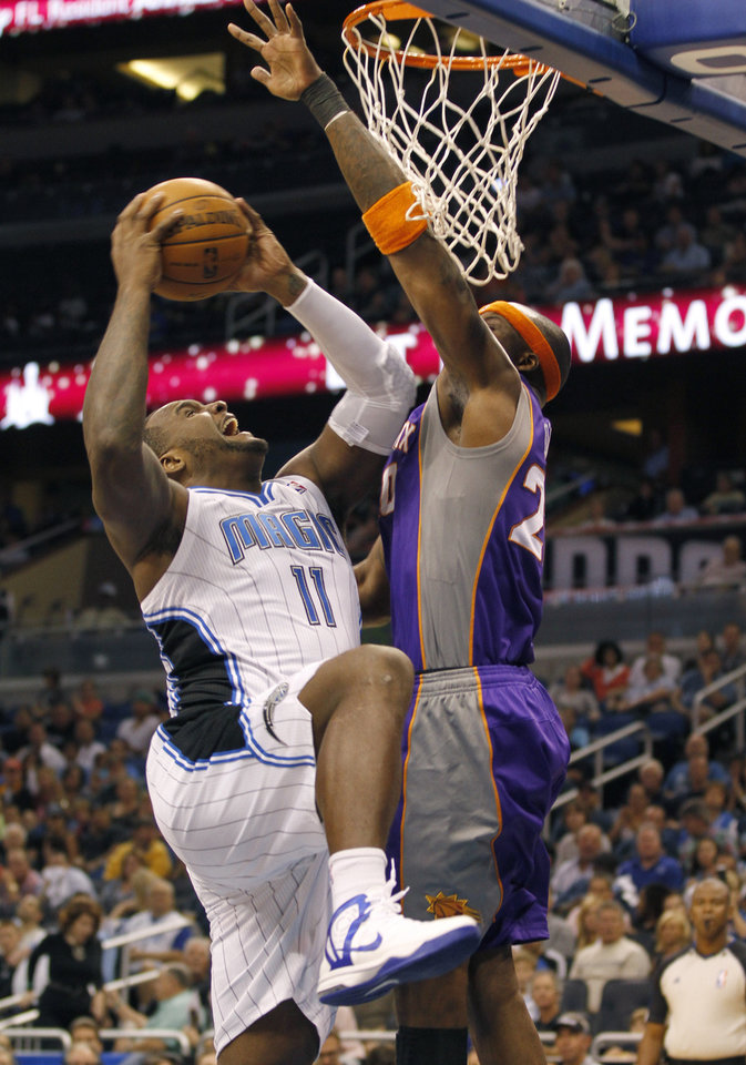 Orlando Magic forward Glen Davis (11) shoots as Phoenix Suns center Jermaine O\'Neal (20) tries to block the shot during the first half of an NBA basketball game in Orlando, Fla., on Sunday, Nov. 4, 2012. (AP Photo/Reinhold Matay)