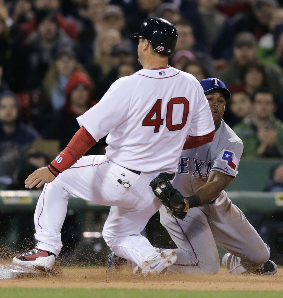 Photo - Texas Rangers third baseman Adrian Beltre can't make the tag in time as Boston Red Sox's A.J. Pierzynski (40) advances to third on a single by teammate Jackie Bradley Jr. during the second inning of a MLB baseball game at Fenway Park, Monday, April 7, 2014, in Boston.(AP Photo/Charles Krupa)