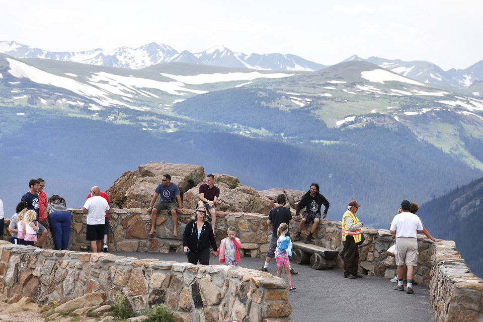 Photo - Visitors take in a scenic overlook off Trail Ridge Road, above tree-line at Rocky Mountain National Park, west of Estes Park, Colo., Monday, July 14, 2014. Lightning killed two people last weekend just miles apart in the popular park, where summer storms can close in quickly with deadly results. (AP Photo/Brennan Linsley)