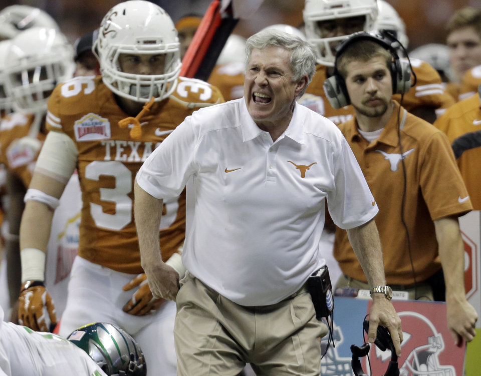 Photo - Texas coach Mack Brown, center, argues a call during the second half of the Valero Alamo Bowl NCAA college football game against Oregon, Monday,  Dec. 30, 2013, in San Antonio. Brown has resigned and the game is his last. (AP Photo/Eric Gay)
