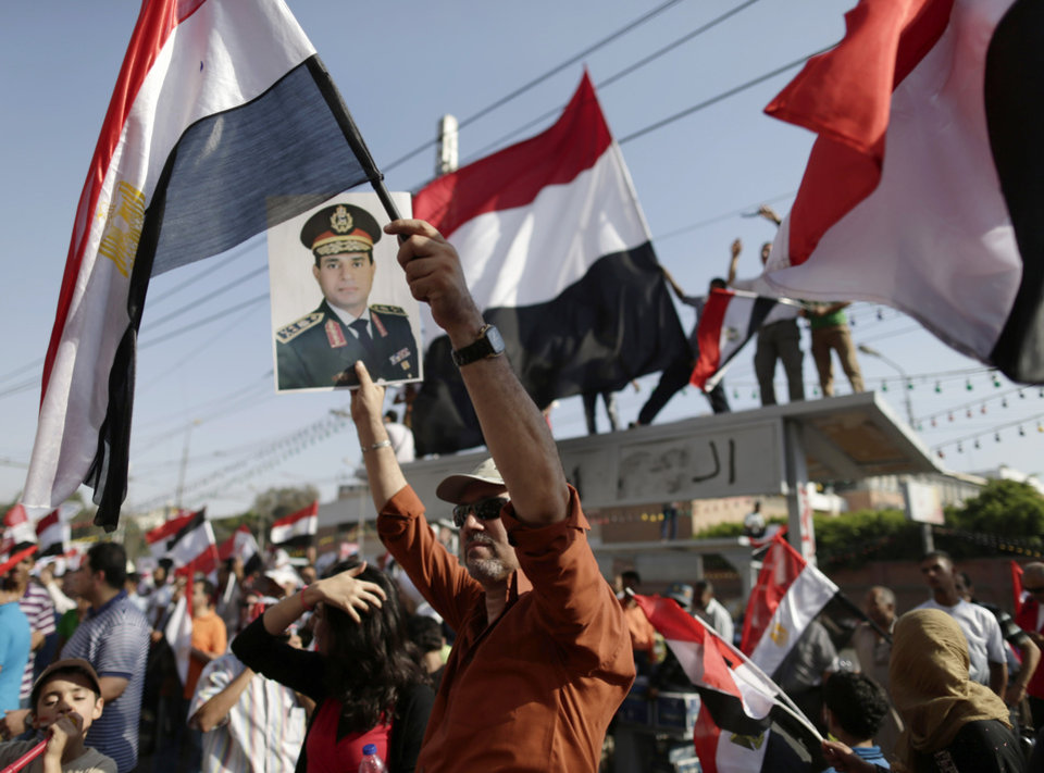 Photo - Demonstrators against Egypt's ousted President Mohammed Morsi chant slogans during a protest by the presidential palace in Cairo, Egypt, Friday, July 26, 2013. Political allies of Egypt's military lined up behind its call for huge rallies Friday to show support for the country's top general, Abdel-Fattah el-Sissi, pushing toward a collision with Islamist opponents who are also rallying to demand the return of Mohammed Morsi, the nation's ousted president. (AP Photo/Hassan Ammar)