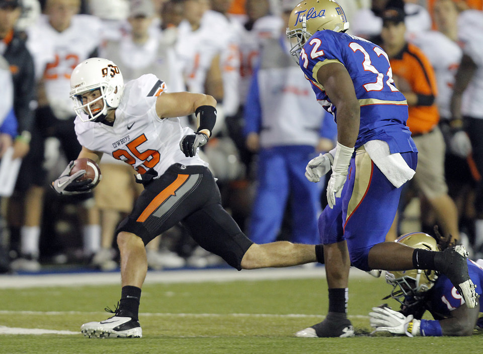 Photo - Oklahoma State's Josh Cooper (25) gets past Tulsa's Curnelius Arnick (32) during a college football game between the Oklahoma State University Cowboys  and the University of Tulsa Golden Hurricane at H.A. Chapman Stadium in Tulsa, Okla., Sunday, Sept. 18, 2011. Photo by Chris Landsberger, The Oklahoman