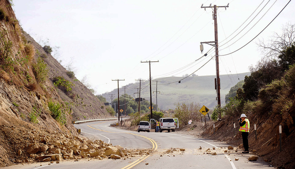 Photo - David Richardson of CalTrans photographs a rock wall where a rockslide closed Carbon Canyon Road near Carbon Canyon Regional Park in Brea, Calif., on Saturday, March 29, 2014, after an earthquake hit Orange County Friday night. More than 100 aftershocks have rattled Orange County south of Los Angeles where a magnitude-5.1 earthquake struck Friday.  Despite the relatively minor damage, no injuries have been reported. (AP Photo/The Orange County Register, Ken Steinhardt)   MAGS OUT; LOS ANGELES TIMES OUT