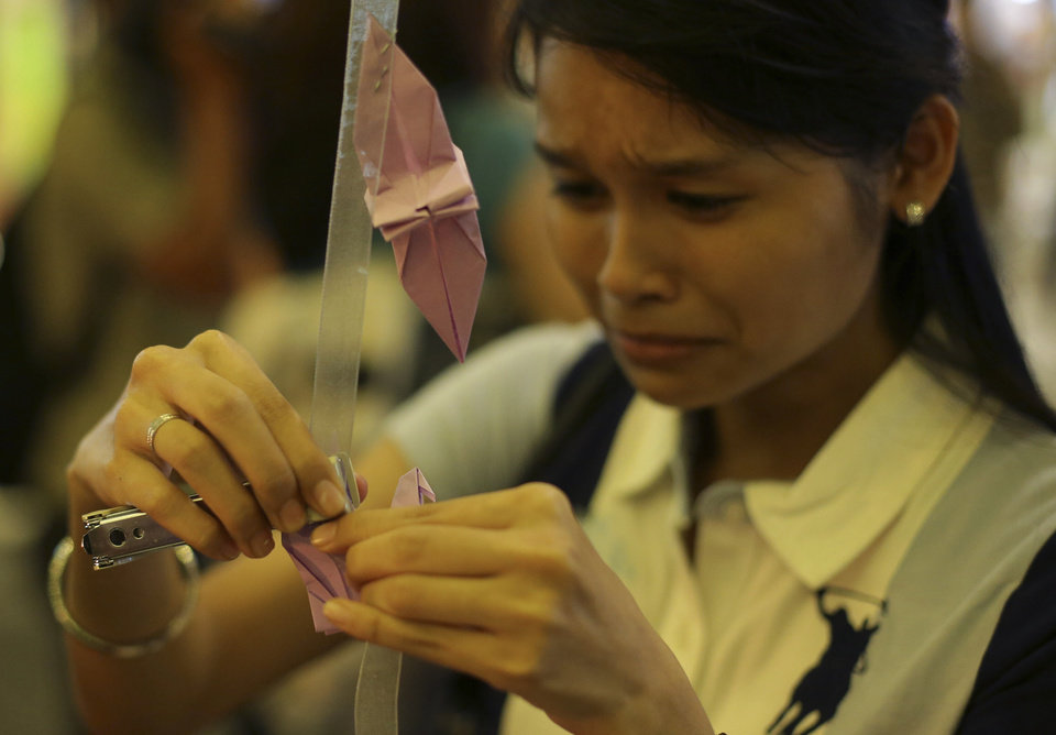 Photo - A woman breaks into tears as she places a paper crane as a symbol for hope and healing during a ceremony in memory of passengers on board the missing Malaysia Airlines Flight MH370 in Kuala Lumpur, Malaysia Thursday, March 27, 2014. Australian officials say search operations for the missing Malaysia Airlines plane have been suspended for the day due to bad weather. (AP Photo/Aaron Favila)