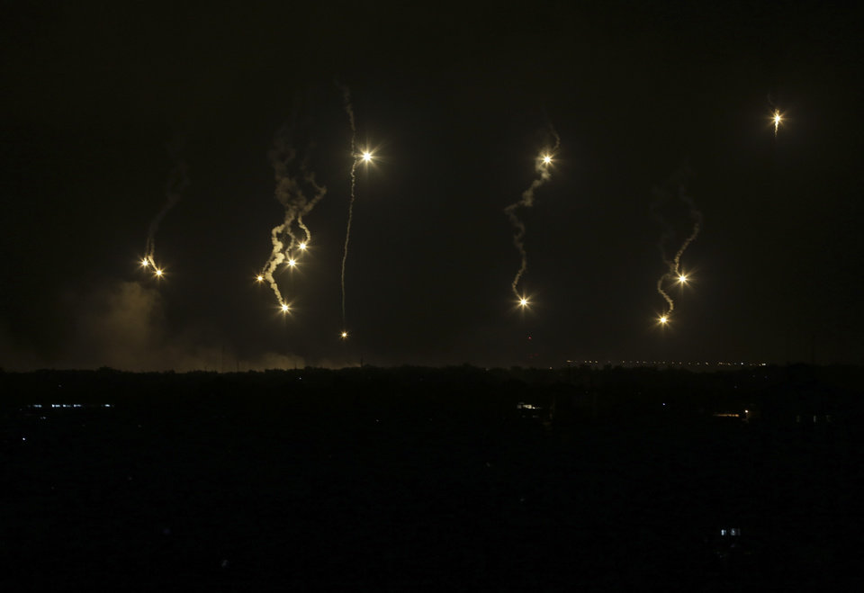 Photo - Israeli forces' flares light up the night sky in the northern Gaza Strip, early Saturday, July 19, 2014. Israeli troops pushed deeper into Gaza on Friday to destroy rocket launching sites and tunnels, firing volleys of tank shells and clashing with Palestinian fighters in a high-stakes ground offensive meant to weaken the enclave's Hamas rulers. (AP Photo/Adel Hana)