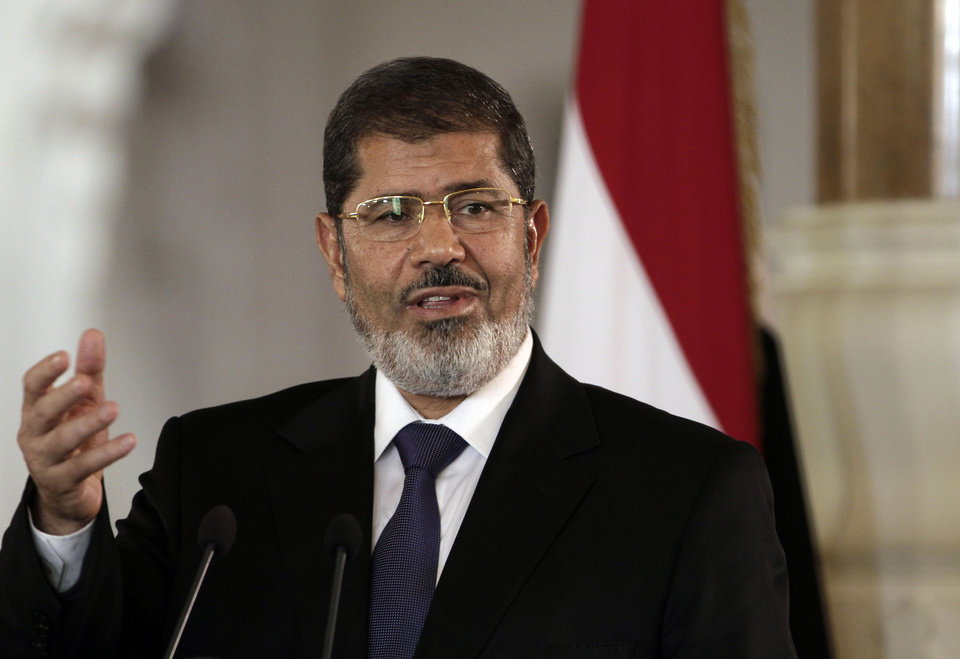 Photo - FILE - In this July 13, 2012 file photo, then Egyptian President Mohammed Morsi speaks to reporters at the presidential palace in Cairo. Egypt's state news agency says Morsi has arrived in Cairo for a trial over prison breaks in 2011. (AP Photo/Maya Alleruzzo, File)