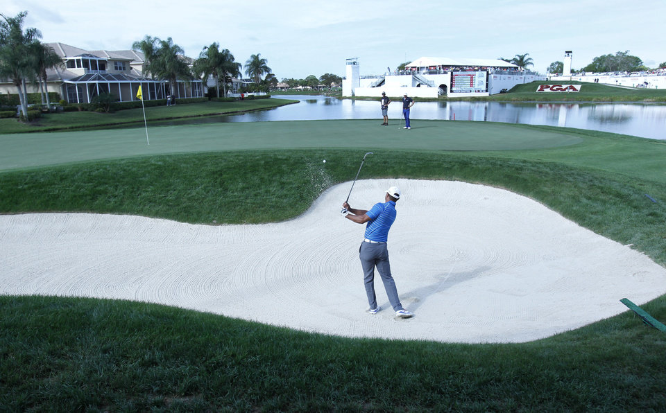 Photo - Golfer Tiger Woods hits out of a bunker on the 17th hole during the first round of the Honda Classic golf tournament, Thursday, Feb. 27, 2014, in Palm Beach Gardens, Fla. (AP Photo/Wilfredo Lee)