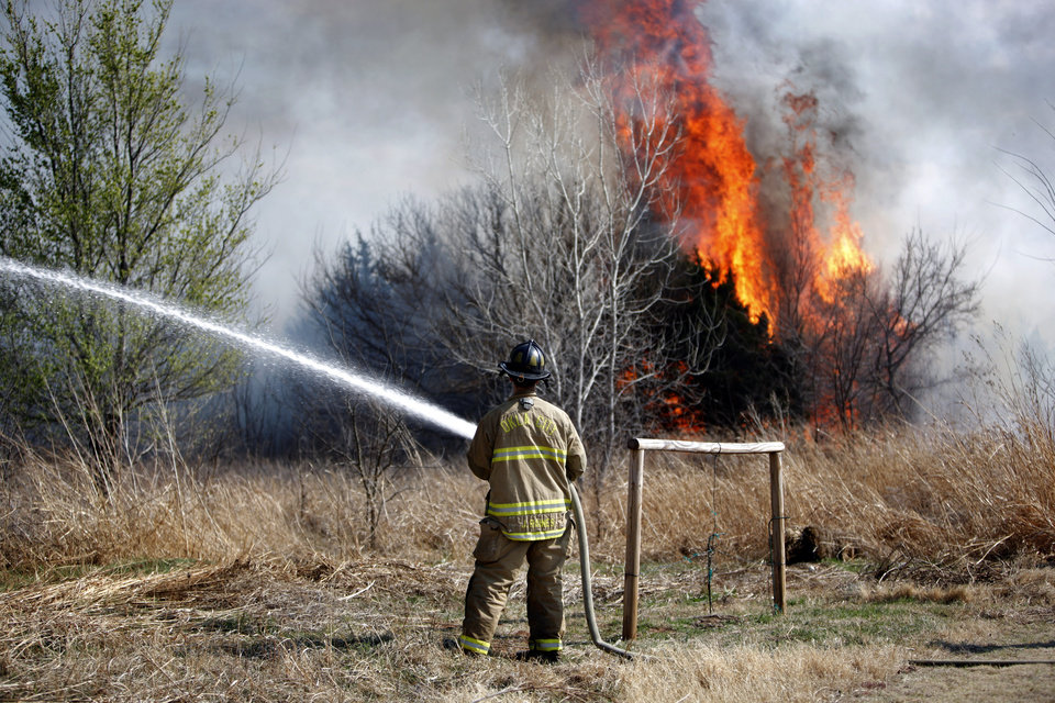 Photo - A firefighter battles a grassfire near a neighborhood at South County Line Road and S.W. 29th, Sunday, March 20, 2011, in Mustang, Okla.. Photo by Sarah Phipps, The Oklahoman