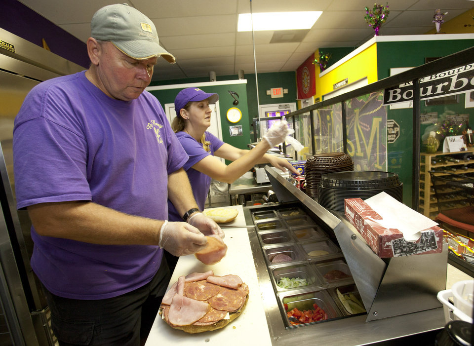 Photo -   In this Friday, Aug. 3, 2012 photo, Walt and Nicole Mazie prepare food at their restaurant, The Big Easy, in Flagler Beach, Fla. Walt Mazie knows it was risky launching a business during hard times. Business was so dismal at first that on some Friday nights, Mazie says, he and his wife sat outside because there were no customers. They held on, though, and about six months ago, there was a turnaround. Mazie says business has increased about 65 percent over last year, thanks to positive publicity and an improved economy. (AP Photo/John Raoux)