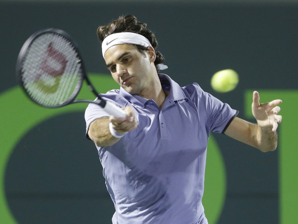 Photo - Roger Federer of Switzerland, returns a shot from Kei Nishikori of Japan, at the Sony Open Tennis tournament, Wednesday, March 26, 2014 in Key Biscayne, Fla. (AP Photo/Wilfredo Lee)