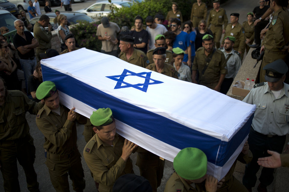 Photo - Israeli soldiers carry the coffin of 2nd Lt. Roy Peles, an infantry officer, during his funeral at Kiryat Shaul military cemetery in Tel Aviv, Israel, Sunday, July 27, 2014. Peles, 21, was killed in combat on Saturday in the Gaza Strip. (AP Photo/Ariel Schalit)