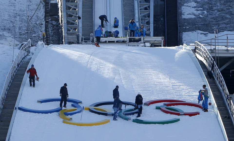 Photo - Workers prepare the hill prior to the first official training for the men's ski jumping prior to the 2014 Winter Olympics, Thursday, Feb. 6, 2014, in Krasnaya Polyana, Russia. (AP Photo/Matthias Schrader)