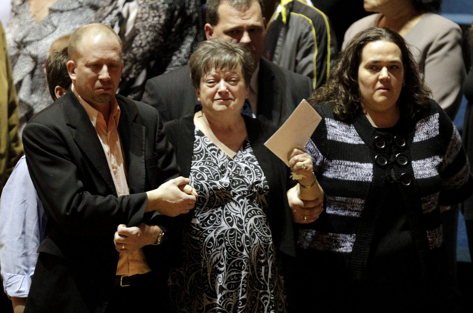 Photo - Jan Poland, center, walks in with son, Aaron and daughter Lydia to join friends and family to pay respects for Charles Albert Poland Jr., at the Ozark Civic Center on Sunday, Feb. 3, 2013, in Ozark, Ala. (AP Photo/Butch Dill)