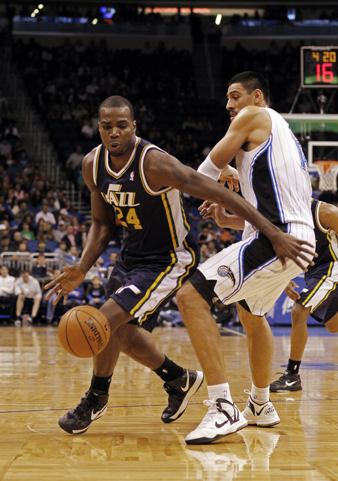 Photo - Utah Jazz power forward Paul Millsap (24) drives around Orlando Magic power forward Gustavo Ayon (19) during the first half of an NBA basketball game, Sunday, Dec. 23, 2012, in Orlando, Fla. (AP Photo/Scott Iskowitz)