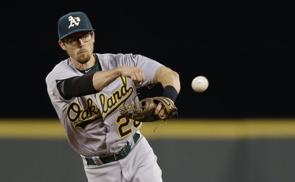 Photo - Oakland Athletics second baseman Eric Sogard throws out Seattle Mariners' Corey Hart at first base to end the third inning of a baseball game, Friday, April 11, 2014, in Seattle. (AP Photo/Ted S. Warren)