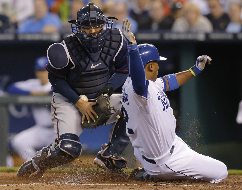 Photo - Kansas City Royals' Alcides Escobar (2) slides safely past Minnesota Twins catcher Kurt Suzuki during the third inning of a baseball game at Kauffman Stadium in Kansas City, Mo., Friday, April 18, 2014. Escobar scored on a single hit by teammate Omar Infante. (AP Photo/Orlin Wagner)