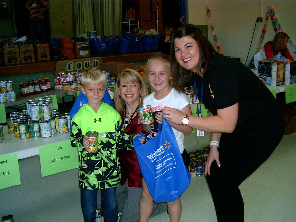 Photo - Clegern second-graders Cole Davenport and Megan Morrison help their teacher Nichole Seay and school counselor Allison Morris, right, fill bags to help children in Oklahoma City. PHOTO BY STEVE GUST, FOR THE OKLAHOMAN