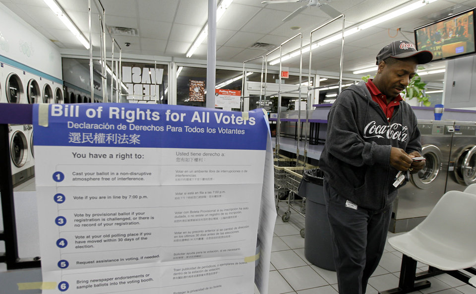 Photo -   Darryl Williams waits to vote inside at the 24-hour Su Nueva Laundromat in Chicago's 13th Ward on Election Day, Tuesday, Nov. 6, 2012, in Chicago. (AP Photo/Charles Rex Arbogast)